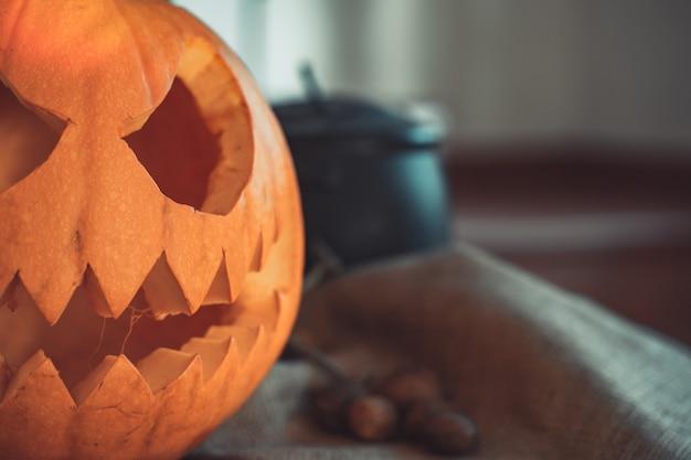 Halloween griezelig pompoengezicht in een tafel met decoratie skeletkaarsen noten