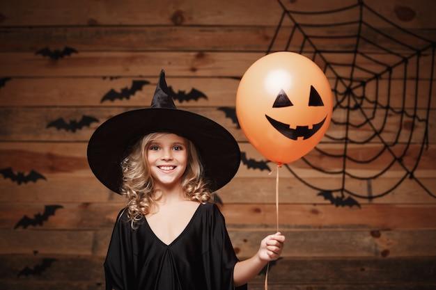 Halloween heks concept - kleine kaukasische heks kind genieten met halloween ballon. over vleermuis en spinnenweb achtergrond.