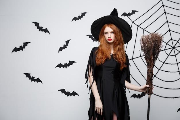 Halloween heks concept portret van mooie jonge heks met bezemsteel over grijze muur met vleermuis en spinnenweb muur