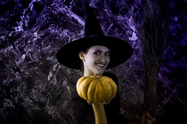 Halloween-heks die een pompoen en een bezem houdt. lachende vrouw gekleed als een feeënheks