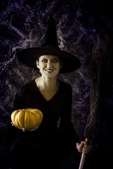 Halloween-heks die een pompoen en een bezem houdt. vrouw gekleed als een feeënheks