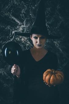 Halloween-heks die een pompoen en een zwarte luchtballon houdt. vrouw gekleed als een feeënheks