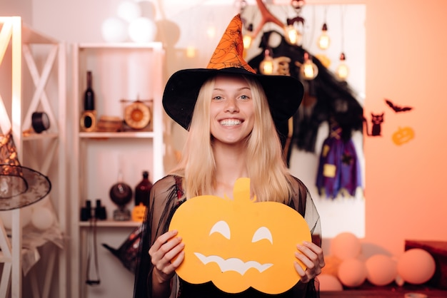 Halloween-heks in zwarte hoed. vrouw poseren met pompoen.