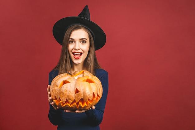 Halloween-heks met een gesneden pompoen - die op rode achtergrond wordt geïsoleerd. emotionele jonge vrouw in halloween-kostuum.