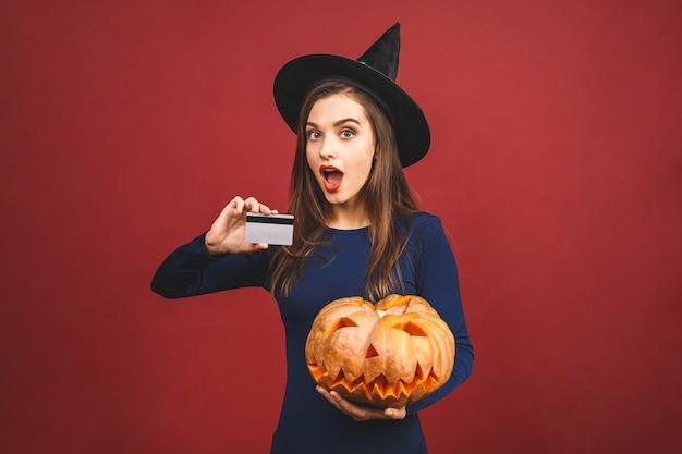 Halloween-heks met een gesneden pompoen en creditcard - die op rode achtergrond wordt geïsoleerd. emotionele jonge vrouw in halloween-kostuum.