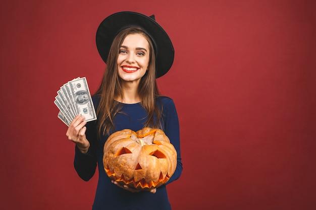 Halloween-heks met een gesneden pompoen en geld - dat op rode achtergrond wordt geïsoleerd. emotionele jonge vrouw in halloween-kostuum.