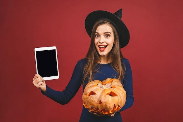 Halloween-heks met een gesneden pompoen en tabletscherm - dat op rode achtergrond wordt geïsoleerd. emotionele jonge vrouw in halloween-kostuum.