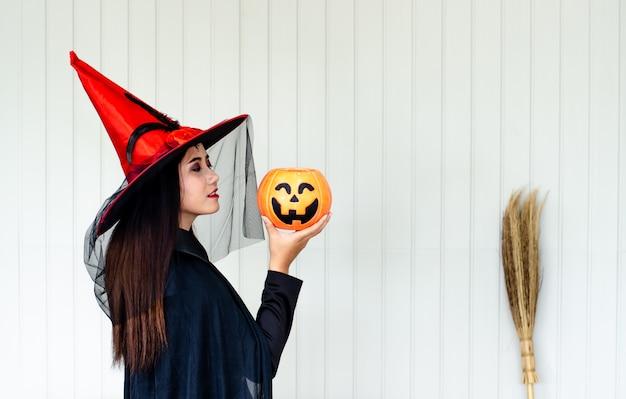Halloween-heks met een magische pompoen, mooie jonge vrouw in heksenhoed en kostuum