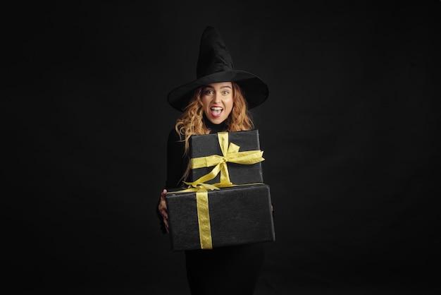 Halloween-heks met een zwarte hoed op een zwarte muur met geschenkdozen