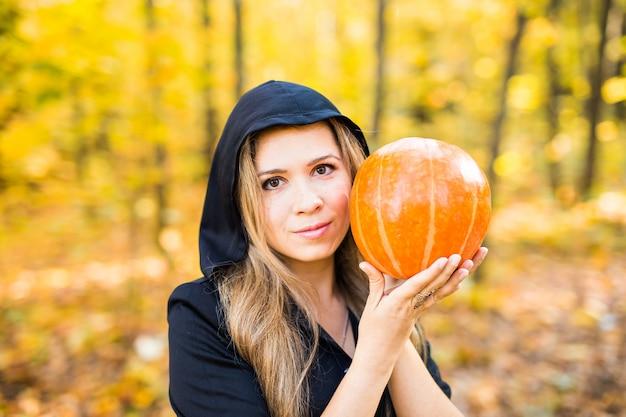Halloween-heks met pompoen in een bos. halloween
