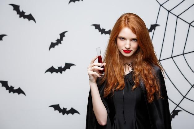 Halloween-heksenconcept - gelukkige halloween-heks die bloed drinkt over donkergrijze muur met vleermuis en spinnenweb.