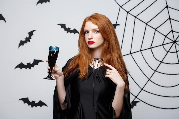 Halloween-heksenconcept - gelukkige halloween-heks die glas bloedige rode wijn houdt over donkergrijze muur met vleermuis en spinnenweb.