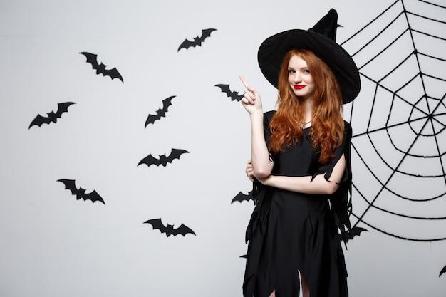 Halloween-heksenconcept - happy halloween-heks die met de vinger aan de zijkant wijst over de donkergrijze muur met vleermuis en spinnenweb.