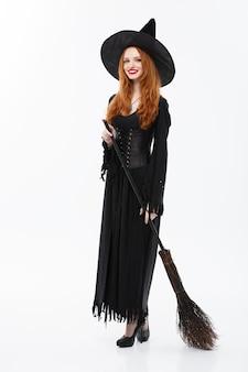 Halloween-heksenconcept van volledige lengte gelukkige elegante heks met bezemsteel voor het vieren van halloween-feest over witte muur