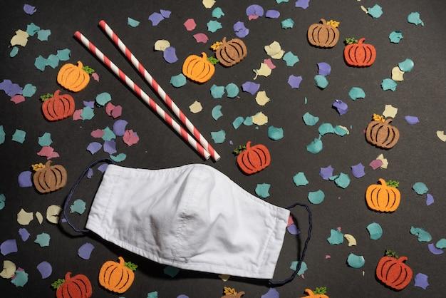 Halloween in coronavirus pandemie met vilten pompoenen, confetti en papieren rietjes met gezichtsmasker