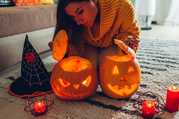 Halloween jack-o-lantaarn pompoenen, vrouw opent pompoenen en kijkt thuis naar binnen