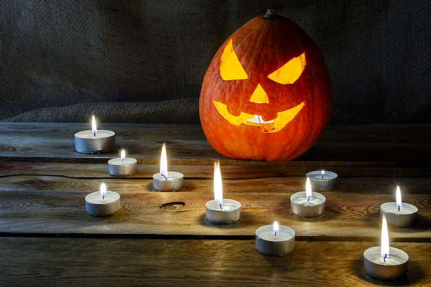 Halloween jack-o-lantern en brandende kaarsen. halloween symbool lachende pompoen achtergrond.