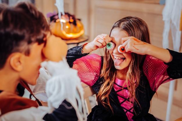 Halloween jurk. gelukkig donkerharige mooi meisje, gekleed in heldere roze en zwarte halloween-jurk met veel plezier