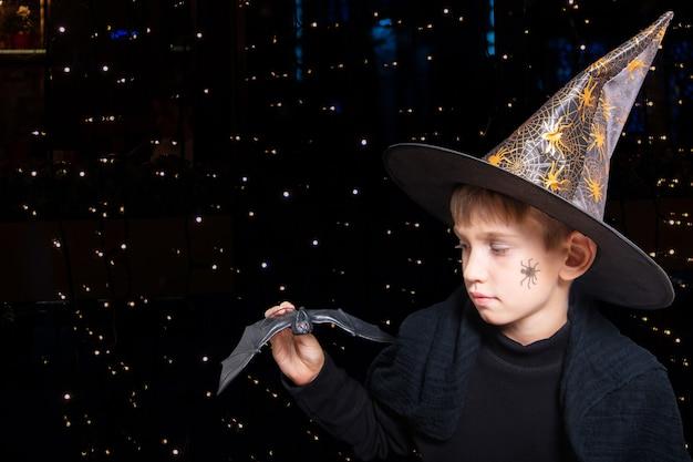 Halloween-kinderen. een jongen in een tovenaarshoed en met een geschilderde spin op zijn wang die een zwarte vleermuis van halloween vasthoudt om iemand bang te maken op een zwarte achtergrond met bokeh. klaar voor de kersttrick or treat.