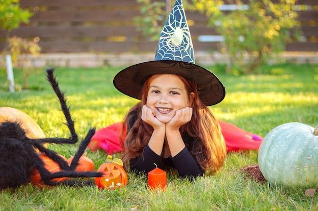 Halloween-kinderen. grappig lachend meisje in een heksenhoed liggend op het gras met oranje pompoenen en een grote zwarte spin buitenshuis.