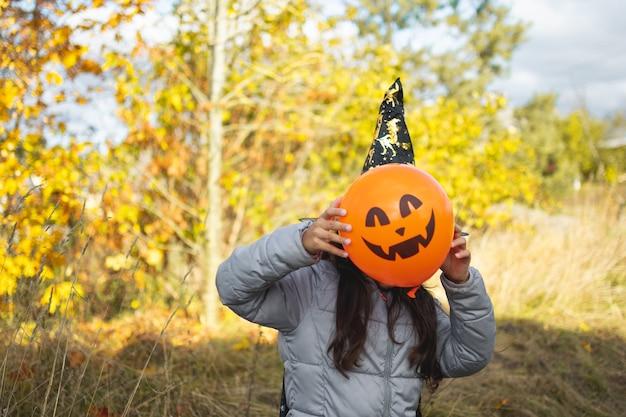 Halloween-kinderen. meisje met jack o 'lantaarn in heksenhoed met pompoen. peuter jongen in heks kostuum spelen in herfst park. een kind in een carnavalskostuum buiten
