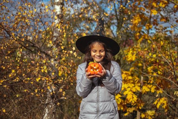 Halloween-kinderen. meisje met jack o 'lantaarn in heksenhoed met pompoen. peuter jongen in heks kostuum spelen in herfst park.