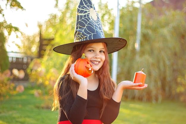 Halloween-kinderen. portret van een grappig glimlachend meisje in een zwarte heksenhoed die een pompoenlamp en een kaars houdt.