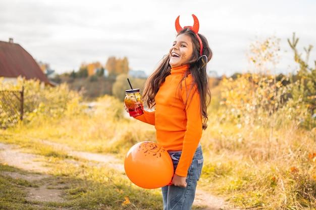 Halloween kinderen. portret van glimlachend meisje met bruin haar rennen en springen. grappige kinderen in carnavalskostuums buitenshuis.