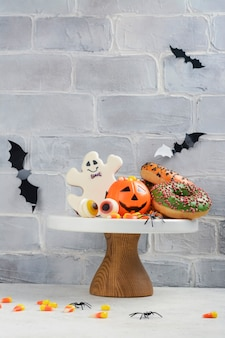 Halloween kinderfeesttafel met snoepkorrels, gemberkoekjes en griezelige donuts.
