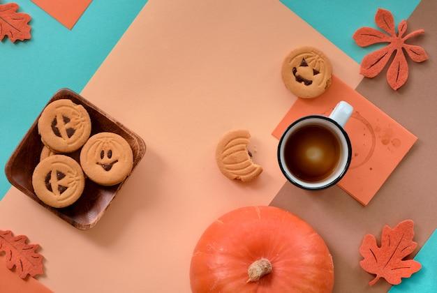 Halloween-koekjes en lege koffie op geometrische achtergrond