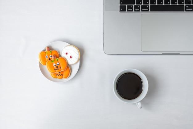 Halloween-koekjes, hete koffie en computerlaptop op witte achtergrond. happy halloween, online winkelen, hallo oktober, herfstherfst, feestelijk, feest- en vakantieconcept