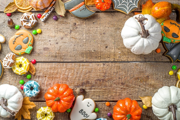 Halloween-koekjes, snoepjes en decorachtergrond. trick or treat-concept. traditionele halloween peperkoek, snoep met pompoenen en decoraties op houten achtergrond bovenaanzicht kopie ruimte