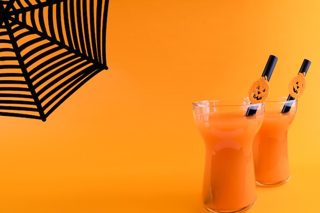 Halloween koolzuurhoudende oranje drank in glas versierd met hefboom-o-lantaarnpompoen