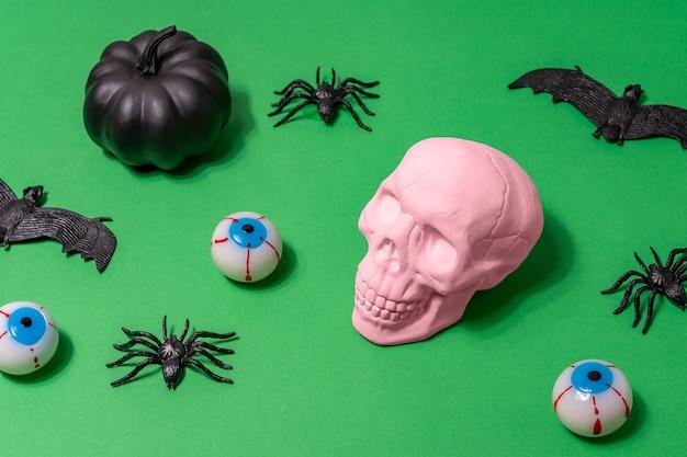 Halloween-lay-out met roze schedelspinnen, vleermuizen en oogbollen op groene achtergrond