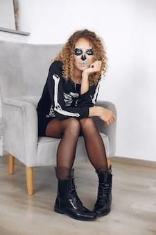 Halloween make-up schedel mooie vrouw met blond kapsel. santa muerte model meisje in zwart kostuum.