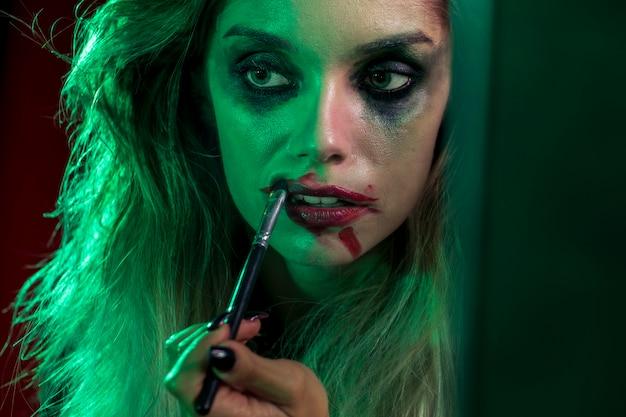 Halloween-meisje dat van de close-up een borstel voor haar lippen gebruikt