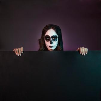 Halloween meisje met make-up achter groot bord
