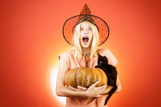 Halloween meisje. vrouw in heksenhoed over sinaasappel