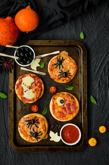 Halloween mini pizza monsters op een zwarte achtergrond. spider pizza, ghost pizza, monster pizza. voedselidee voor halloween-feest.