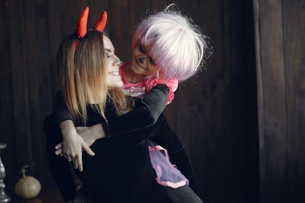 Halloween. moeder en dochter in halloween-kostuum. familie thuis.