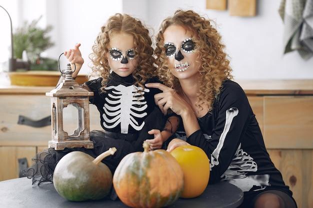 Halloween. moeder en dochter in halloween-kostuum in mexicaanse stijl. familie thuis met pompoenen.