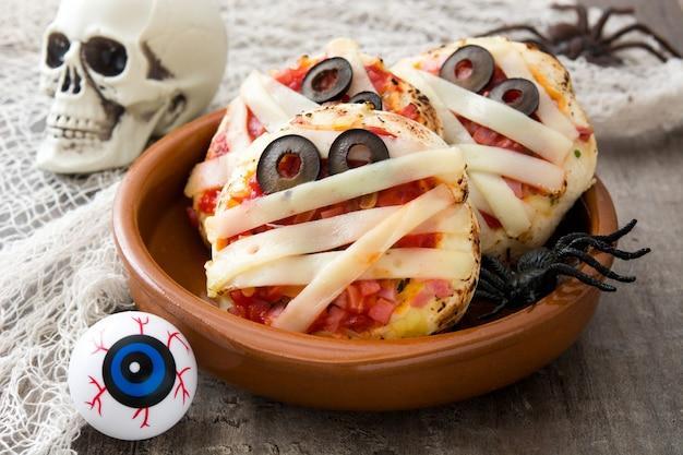 Halloween-mummies minipizza's op houten lijst