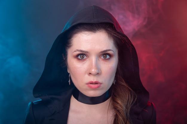 Halloween, mysterieus en myst concept - sexy brunette vrouw in zwarte kap.