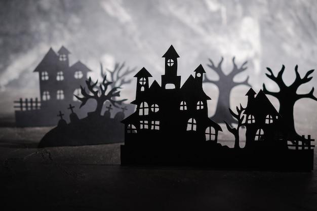 Halloween nacht achtergrond. papieren kunst. verlaten dorp in een donker mistig bos