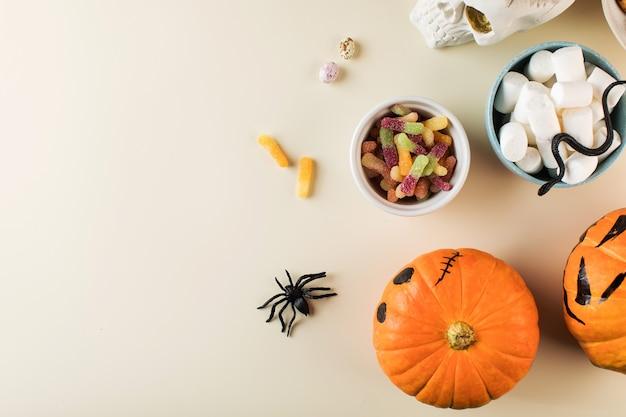 Halloween-ontwerp met zoete lekkernijen, pompoenen met enge gezichten en kopieerruimte op beige achtergrond