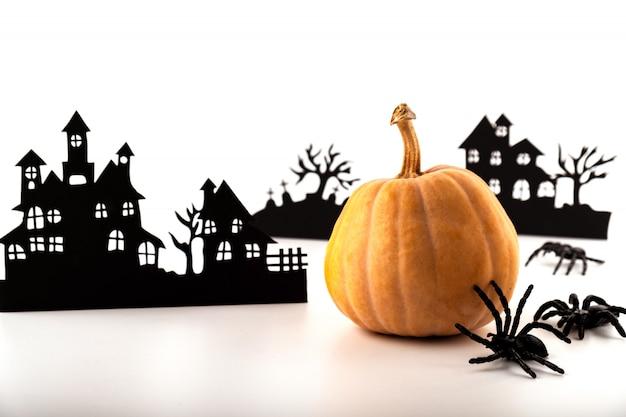 Halloween papier kunst. verlaten dorp en pompoen op wit.