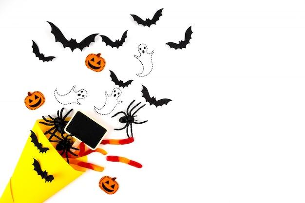 Halloween papier kunst. vliegende zwarte papieren vleermuizen, kevers en spinnen, snoep, pompoenen en spoken op wit.