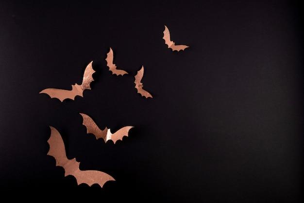 Halloween papier kunst. vliegende zwarte papieren vleermuizen op zwart