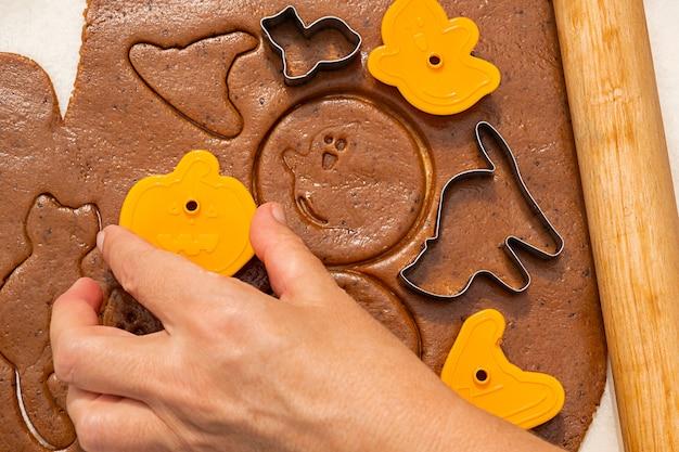 Halloween peperkoek koken. snoepjes met koekjesmessen, vrouwenhand maakt koekjesdeeg