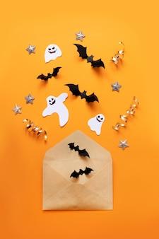 Halloween plat lag samenstelling van vlot papieren envelop en zwarte papieren vleermuizen vliegen omhoog op een oranje achtergrond, bovenaanzicht.